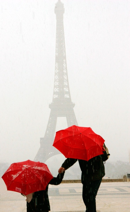red umbrellas at the eiffel tower in during a hail storm......